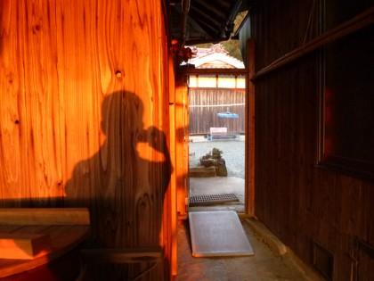 私設公民館煙会所の板壁に映った私の影