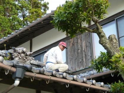 屋根の上で応急修理をする従兄弟の左官さん