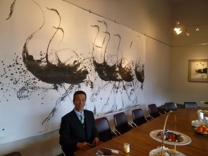 福井江太郎さんが描いたダチョウ絵の前で